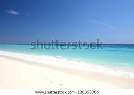 Beautiful beach with crystal clear blue waters of the Andaman sea against blue sky at Koh Rok or Rok island, Thailand - stock photo