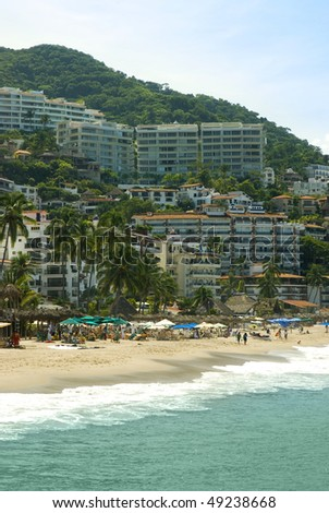 Beautiful beach with hotels, condominiums and palm trees in Puerto Vallarta, Mexico - stock photo