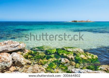 Beautiful beach with turquoise water and stones. Malia, Crete island, Greece.  - stock photo