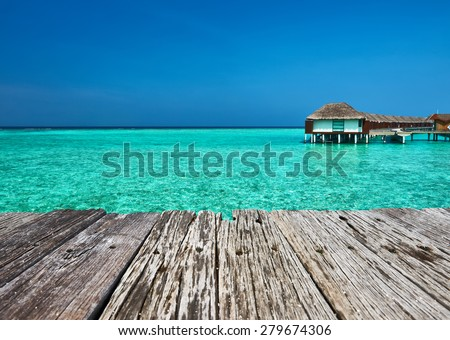 Beautiful beach with water bungalows and old wooden pier at Maldives - stock photo