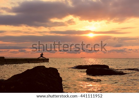 beautiful beautiful sunrise over the sea. Beautiful sky with beautiful clouds. Silhouette of man on the pier in for sports, yoga at dawn. Sun rays through the clouds at dawn  - stock photo