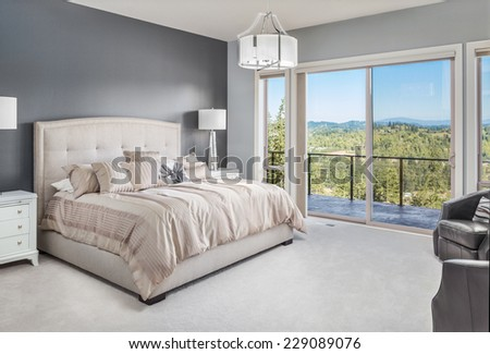 Beautiful Bedroom in Luxury Home with View of Forest and Blue Sky - stock photo