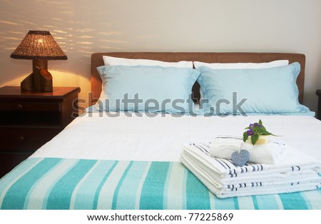 Beautiful bedroom interior with white sheets and striped towels - stock photo