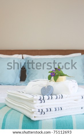 Beautiful bedroom interior with white sheets and striped towels with soap and flowers - stock photo