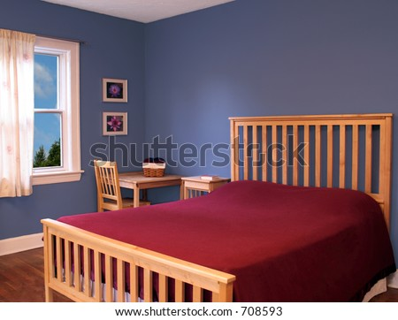 Beautiful bedroom with blue walls and a red bedspread.
