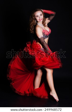 Beautiful belly dancer girl is wearing a black and red fashion costume with wings. Isolated on black