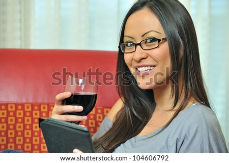 Beautiful bi-racial woman (Asian and Caucasian) resting on red chair holding a glass of red wine while looking at tablet computer - smiling - stock photo