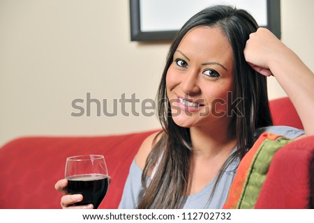 Beautiful bi-racial woman (Asian and Caucasian) resting on red sofa holding a glass of red wine - smiling - stock photo