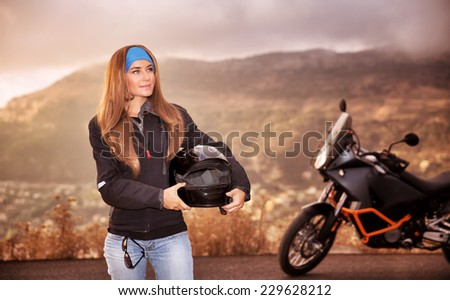 Beautiful biker girl standing on the road with helmet in hands near motorbike, traveling in overcast weather along high mountains, active lifestyle concept - stock photo