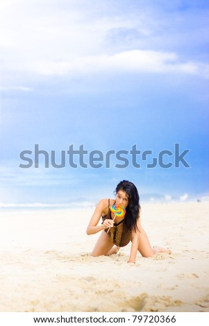 Beautiful Bikini Female Enjoying The Taste Of A Colorful Candy Lollipop On The Beach In Front Of A Vast Expanse Of Open Blue Sky