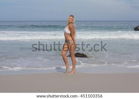 Beautiful Bikini model posing on the beach - stock photo