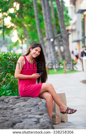 Beautiful biracial Asian Caucasian teen in red dress with cellphone sitting in Hawaii with palm trees and shopping area in background - stock photo