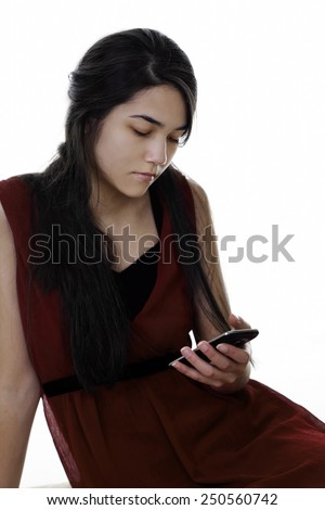 Beautiful biracial teen girl in red dress looking at cell phone in hand, texting or reading - stock photo