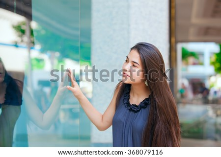 Beautiful biracial teen girl window shopping in urban area, outside large store window - stock photo