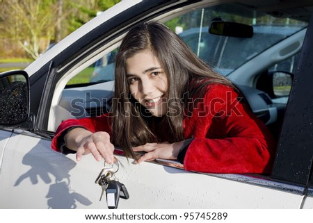 Beautiful biracial teenage girl in driver's seat holding keys to white car - stock photo