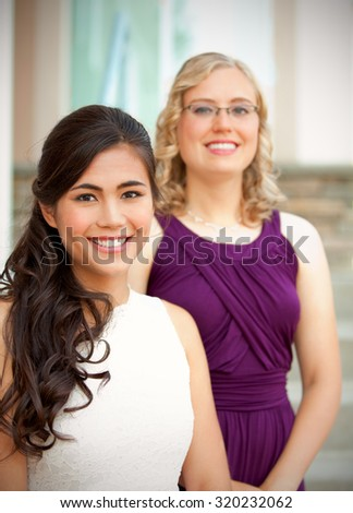 Beautiful biracial young bride smiling with her multiethnic group of bridesmaids in purple dresses - stock photo
