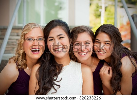 Beautiful biracial young bride smiling with her multiethnic group of bridesmaids in purple dresses, heads together - stock photo