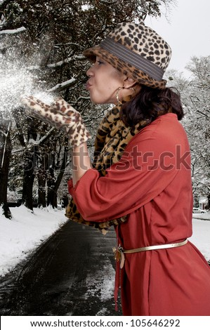 Beautiful black African American woman blowing snow off of her hands - stock photo