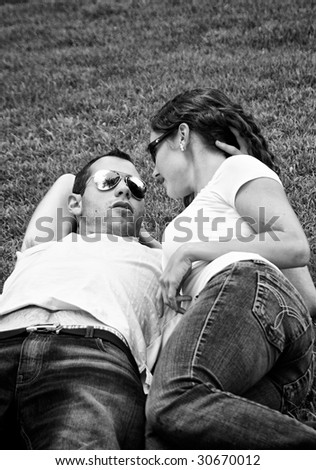 beautiful black and white of young punk lovers laying on the grass wearing sunglasses and talking - stock photo