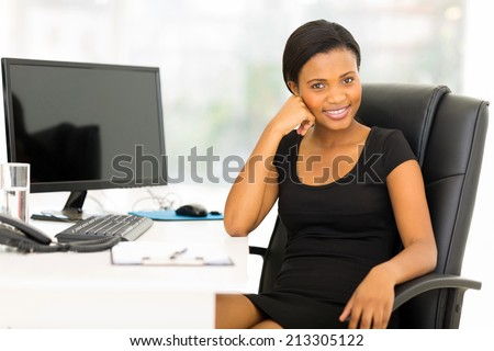 beautiful black businesswoman sitting in office - stock photo