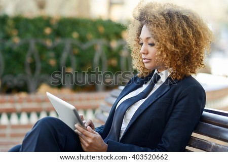 Beautiful black curly hair african woman using tablet computer on an urban bench. Businesswoman wearing suit with trousers and tie, afro hairstyle.