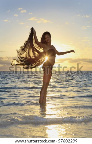 beautiful black female dancer standing in the ocean at sunrise in the tropics - stock photo