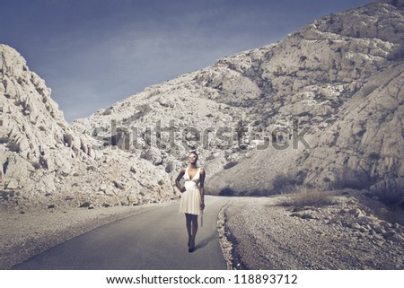 Beautiful black girl, with a white dress, walking on a long road of mountains - stock photo