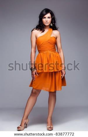 beautiful black hair woman in elegant orange dress, studio shot, full body shot - stock photo