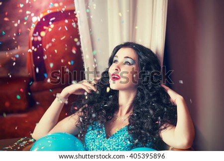 Beautiful black-haired girl sitting in a bathtub filled with blue balloons, and it pours colorful confetti, bachelorette party, cocktail party, smile - stock photo