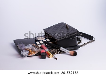 Beautiful black makeup bag and cosmetics isolated on white - stock photo