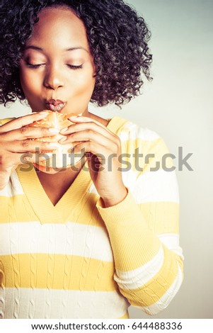 Beautiful black person eating hamburger sandwich