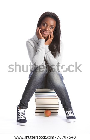 Beautiful black student girl on top of her school work. Smiling and sitting on a pile of books, girl is wearing grey hoodie sweater, blue jeans and sneakers. - stock photo