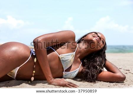 Beautiful black woman lying on the beach - stock photo