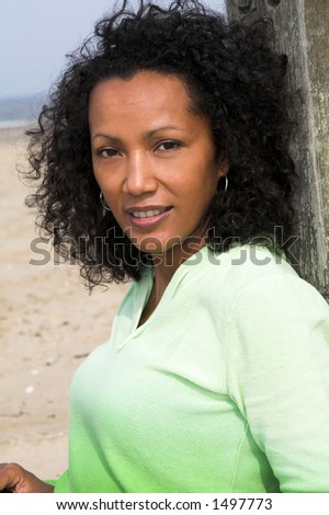 Beautiful black woman outdoors enjoying a day at the beach