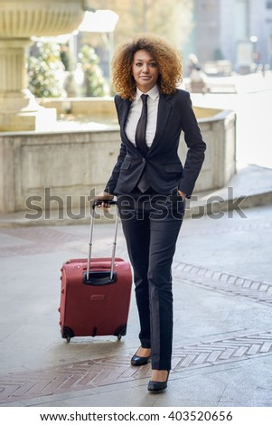 Beautiful black woman smiling and carrying a rolling suitcase in urban background Businesswoman wearing suit with trousers and tie, afro hairstyle. - stock photo