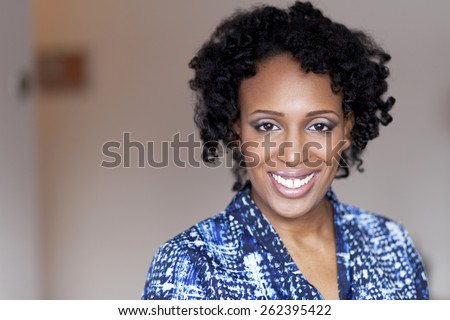 Beautiful black woman smiling at the camera - stock photo