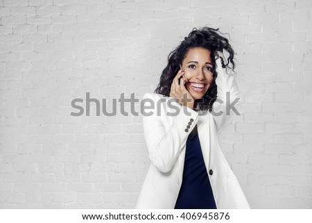 Beautiful black woman speak by mobile phone in white suit, brick wall - stock photo