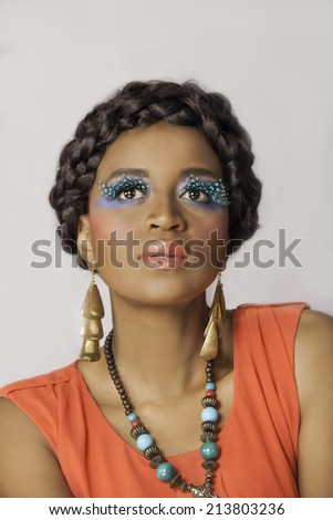 Beautiful black woman with gold earrings, braided hair, necklace and colorful makeup with fun false eyelashes - stock photo