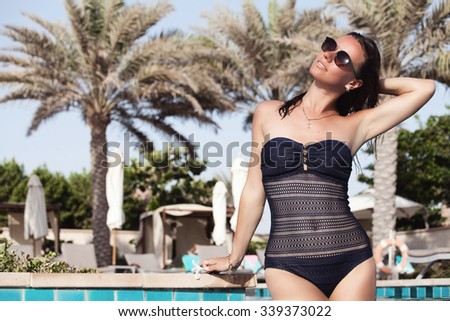 Beautiful blissful woman in bikini enjoying swimming pool and exotic summer luxury vacation. Vacations And Tourism Concept. - stock photo