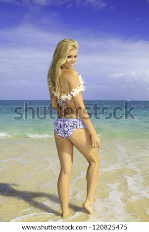 beautiful blond at a hawaii beach wearing a flower lei