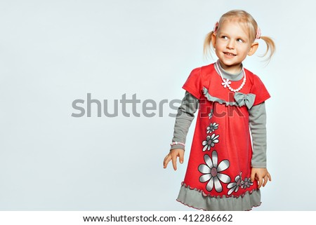 Beautiful blond baby girl on white background looks toward - stock photo