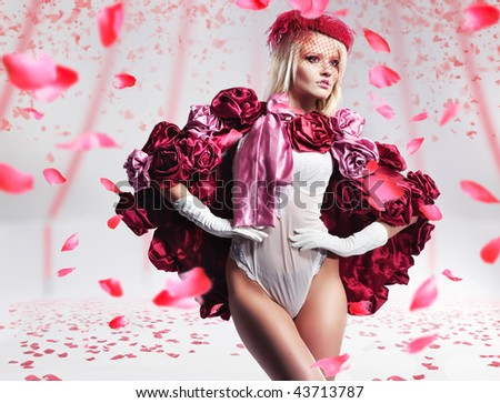 Beautiful blond beauty over flying rose petals - stock photo