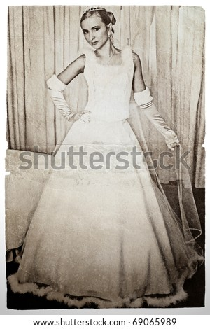 beautiful blond bride in long wedding dress and veil wearing gloves on grunge background. - stock photo