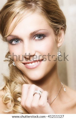 Beautiful Blond bride with blue eyes wearing diamond jewelery