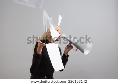 Beautiful blond businesswoman makes passionate presentation holding some papers and loudspeaker in her hands