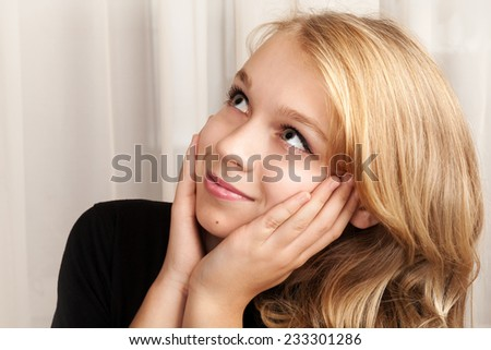 Beautiful blond Caucasian girl is looking up with smile, closeup studio portrait - stock photo