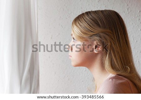Beautiful blond Caucasian girl looking in a window with white curtains, close up portrait - stock photo
