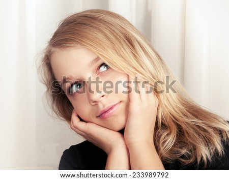 Beautiful blond Caucasian girl looks up with smile, closeup studio portrait - stock photo