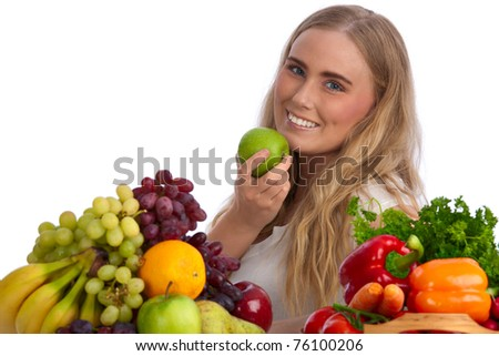 Beautiful blond caucasian young woman smiling and eating a green apple among fruits and vegetables - stock photo