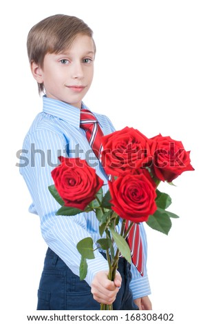 Beautiful blond child wearing formal shirt and a tie stretching red roses (valentine gift concept)  - stock photo